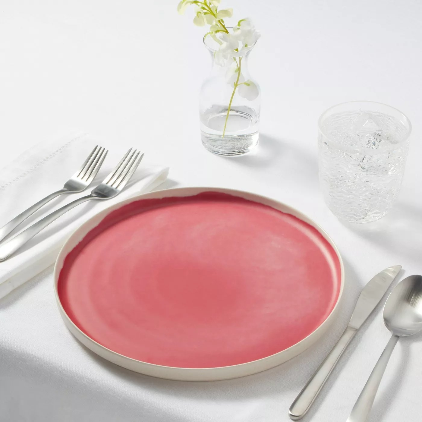 The bright pink plate is on an all white table setting