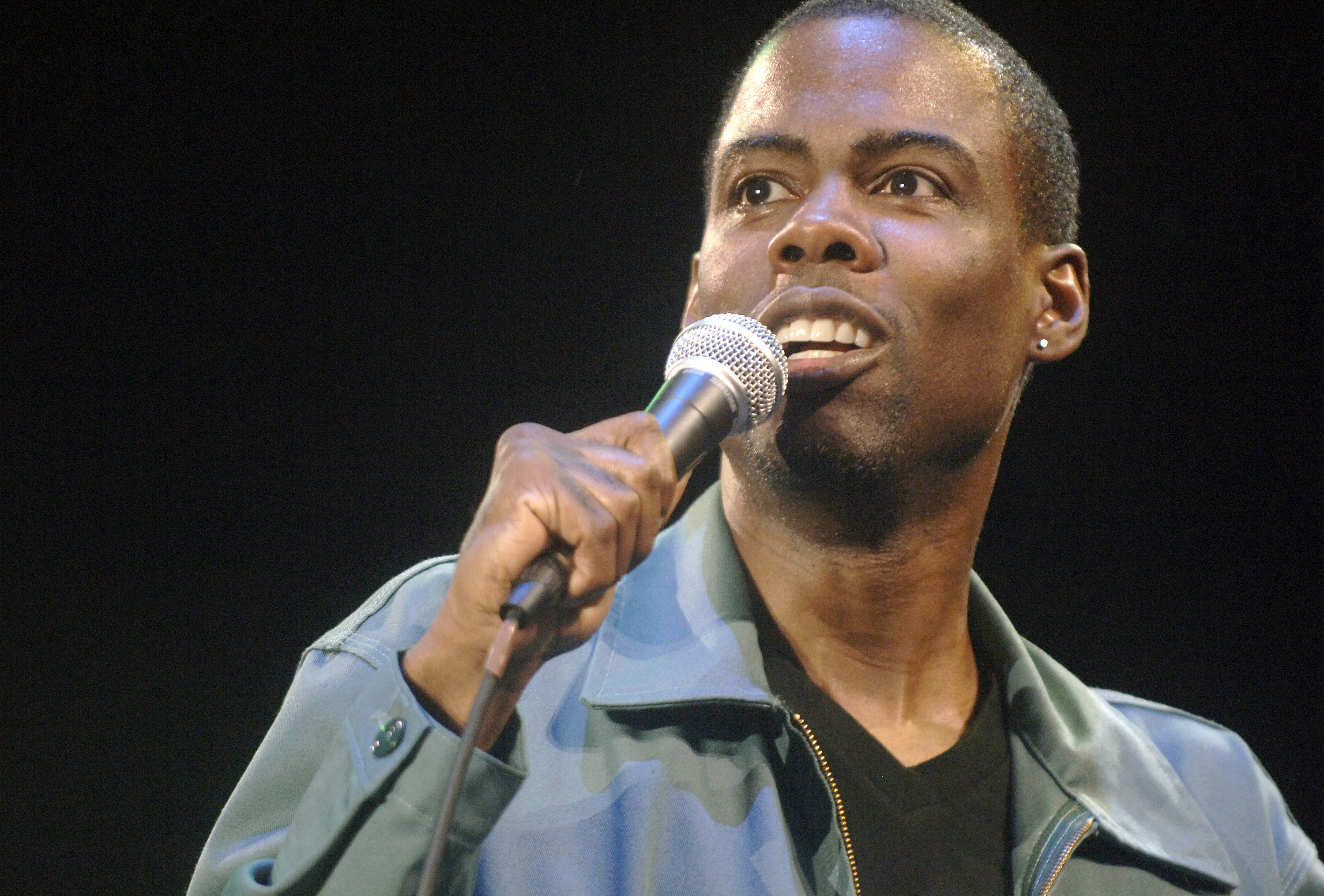 Chris Rock onstage speaks into the microphone
