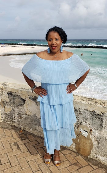 A reviewer wearing the midi dress, which is made up of four tiers, in light blue