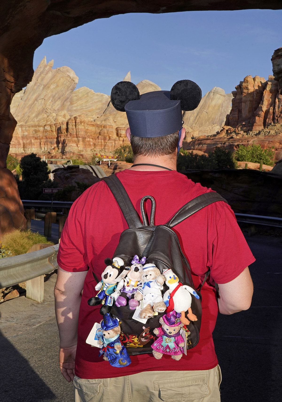 A man photographed from behind wearing Mickey ears and a backpack full of Disney keychains