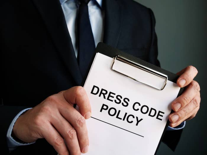 """Man holding a clipboard reading, """"dress code policy"""""""