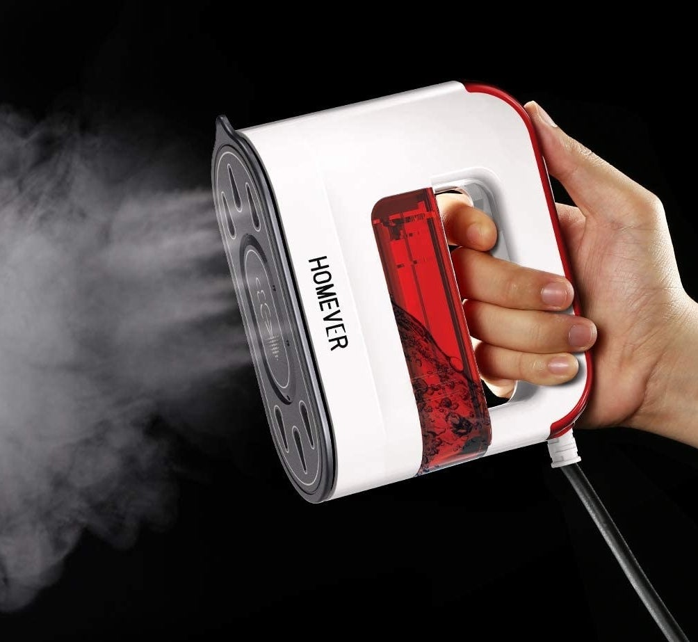 A person holding the handheld steamer while it blows out steam