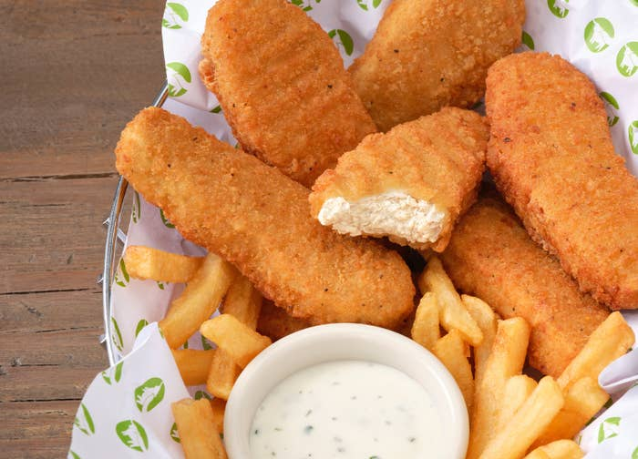 chicken nuggets in a basket with fries and dipping sauce