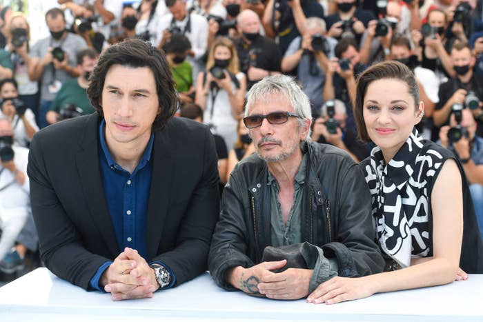 Adam Driver, Leos Carax, and Marion Cotillard are photographed together during the Cannes Film Festival