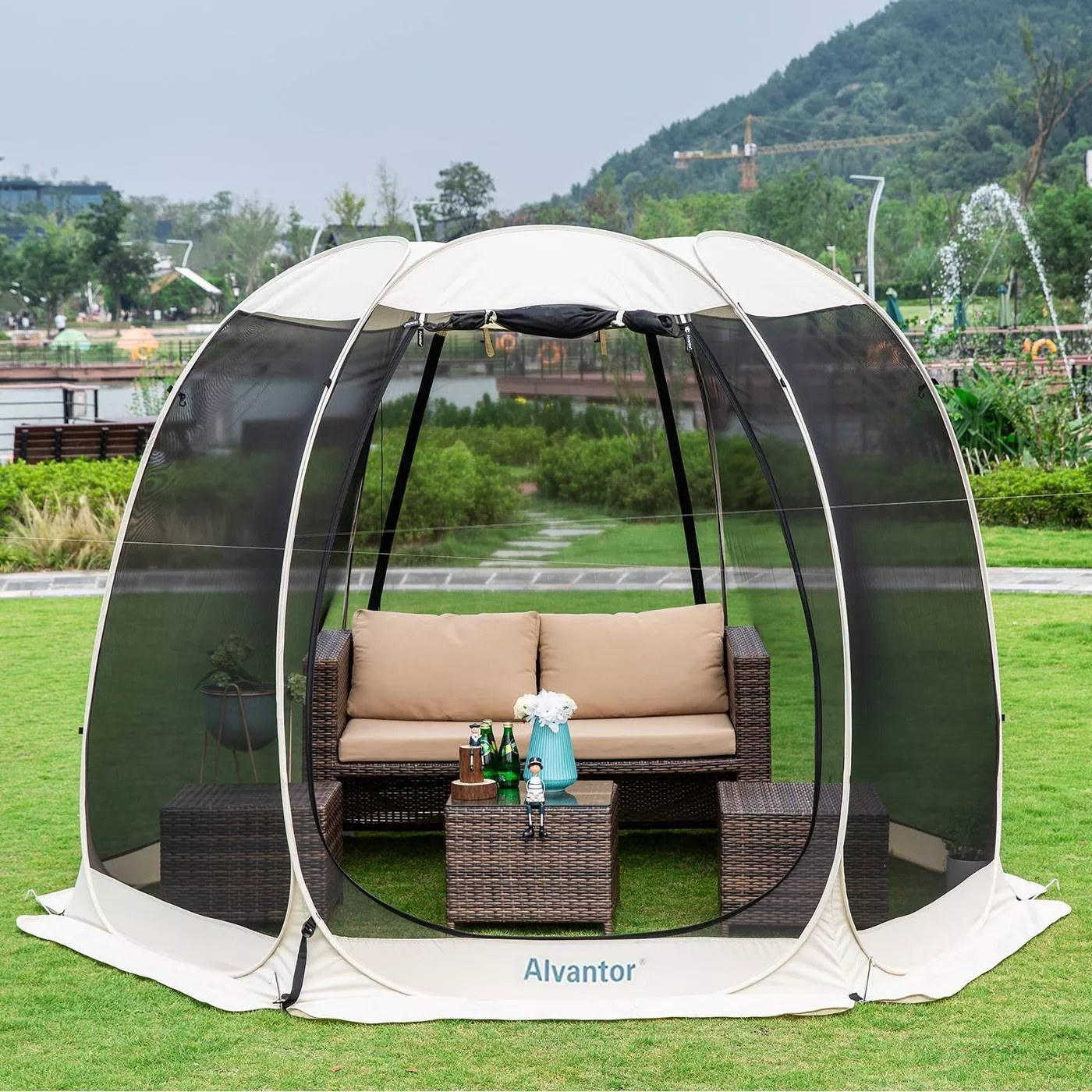 """The pop-up gazebo tent is outside and says """"Alvantor"""" and has porch furniture inside"""