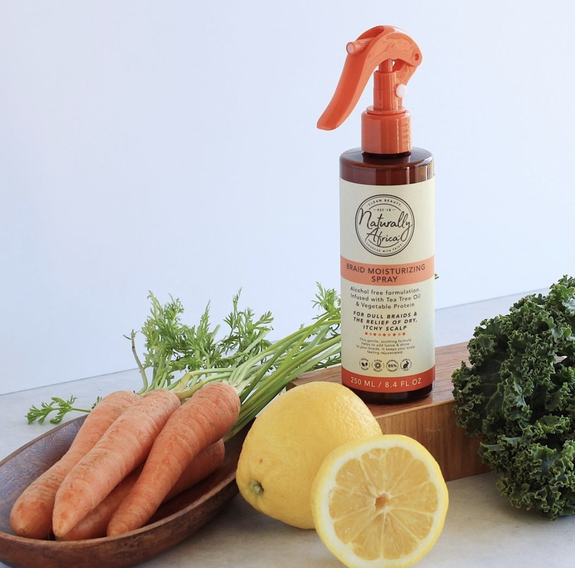 A bottle of braid spray with cut lemons and carrots