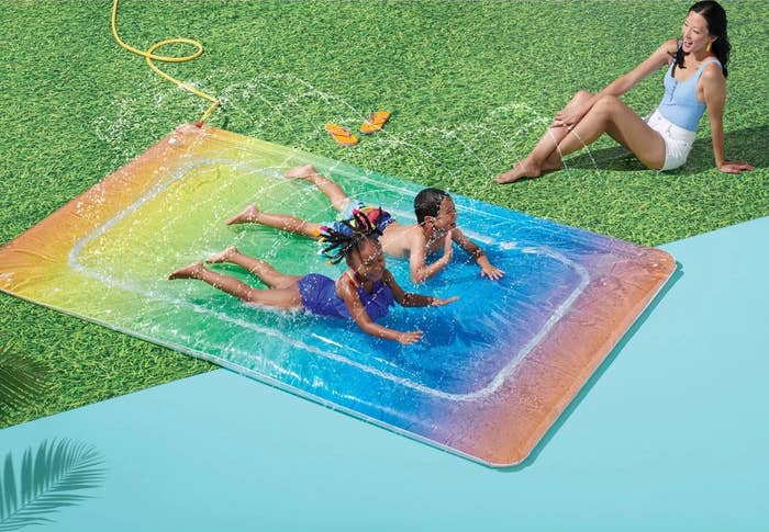 The rainbow blob has two children sliding on top and an adult sitting on the ground nearby