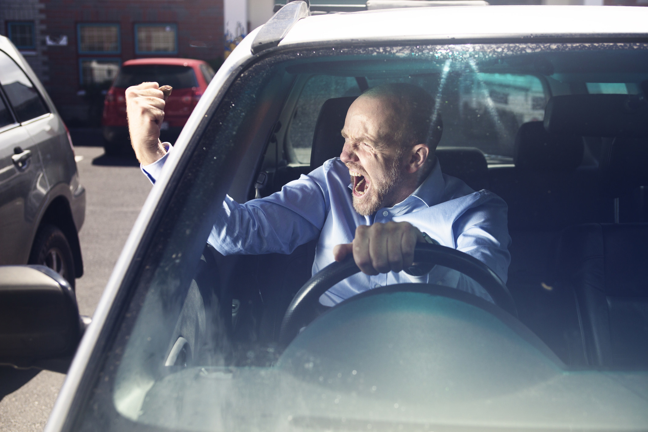 angry man driving and yelling at another car