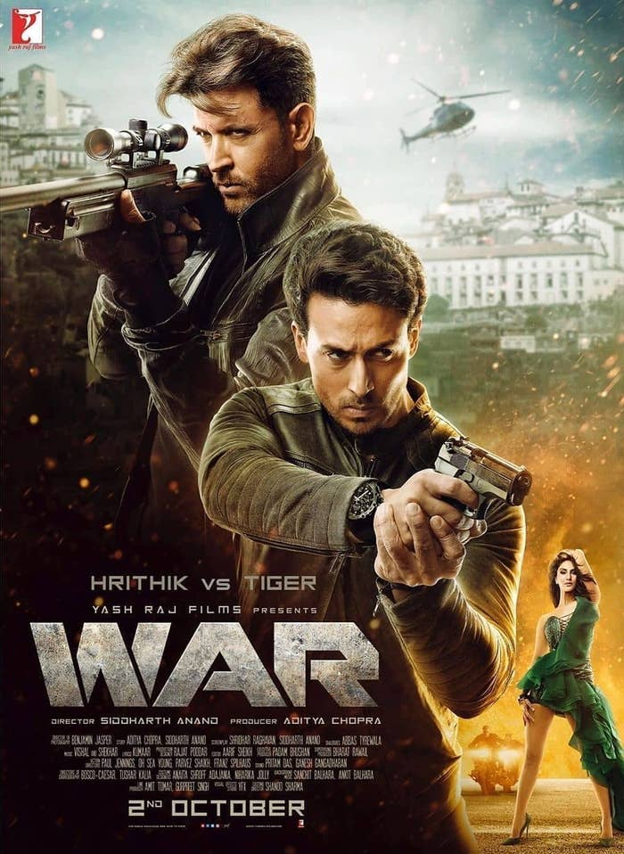 The poster of the movie war in which hrithik roshan and tiger shroff brandish guns while vaani kapoor's character poses seductively
