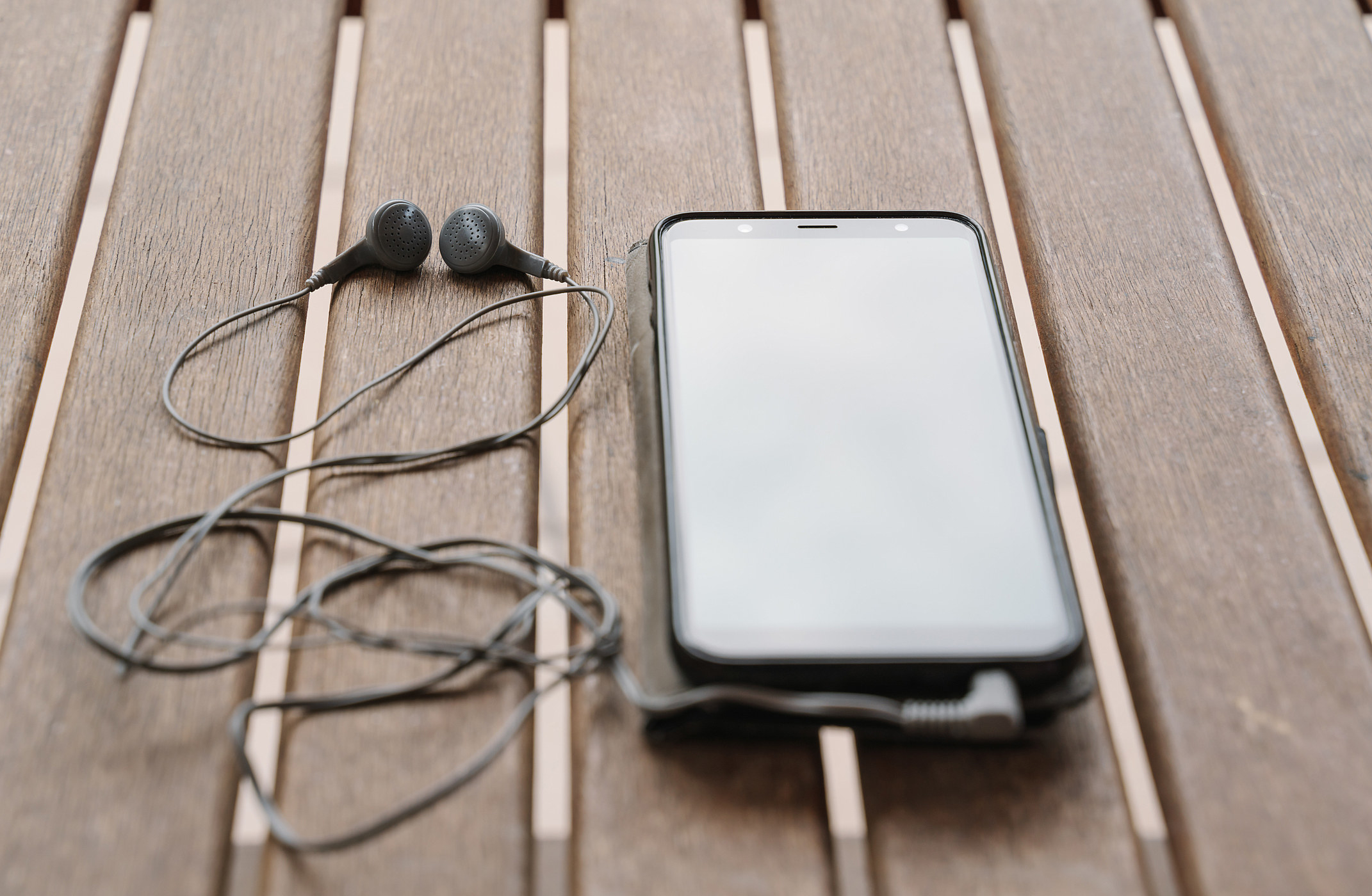 A phone with earbuds plugged in