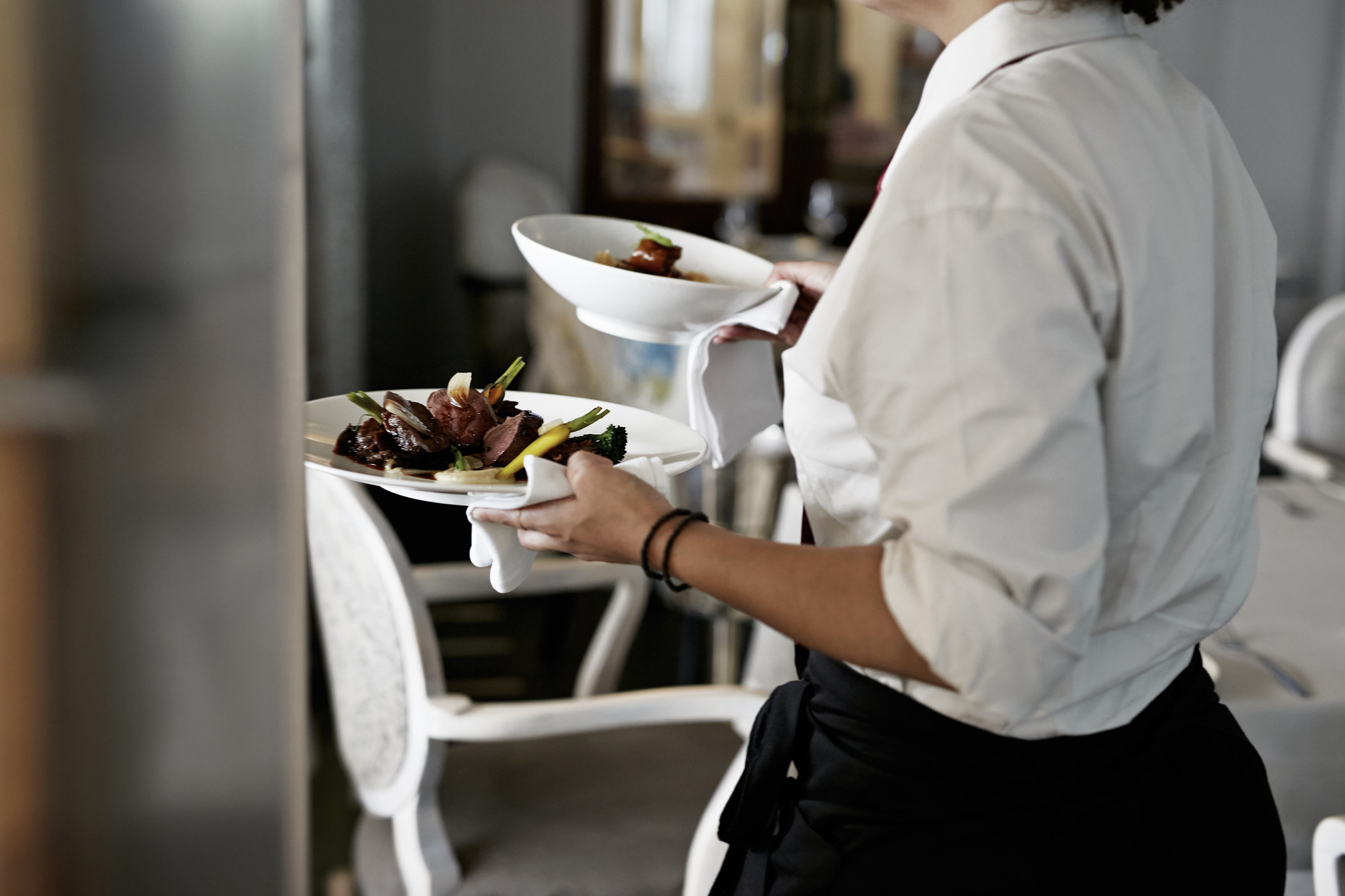 A server carries two dishes in a restaurant