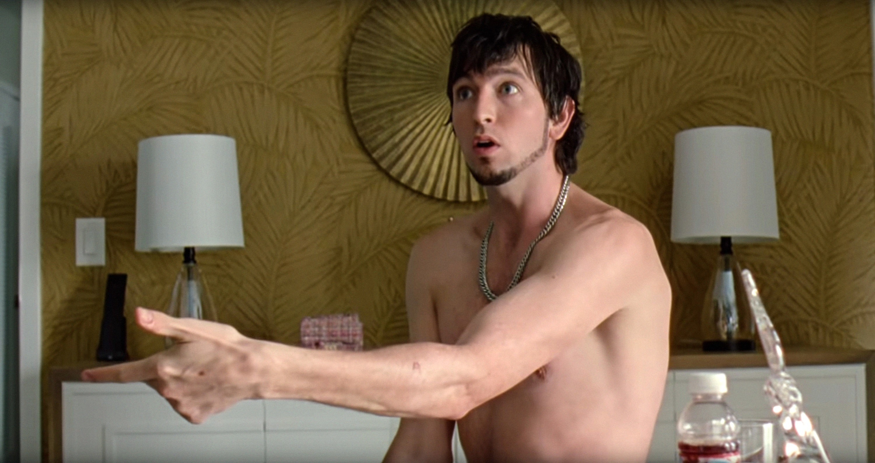 Derrek topless and sitting in a hotel room