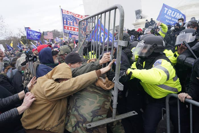 Trump supporters push a metal gate into a line of a police