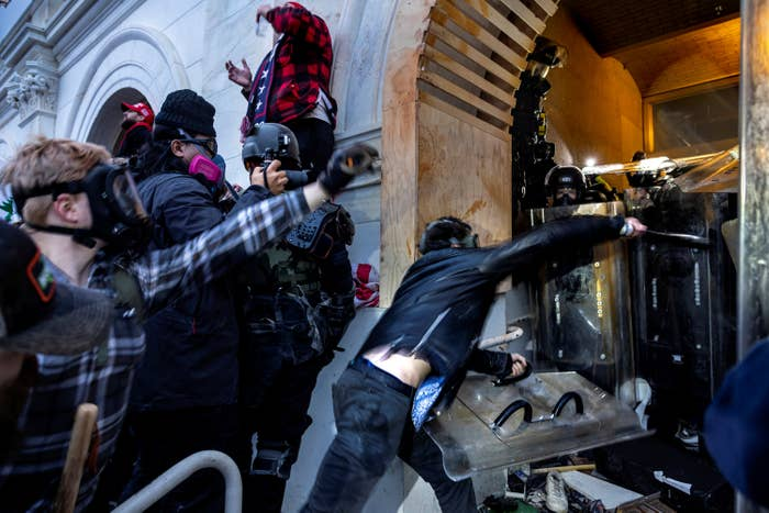 Trump supporters in riot gear try to push past a line of police holding shields blocking a door at the Capitol building