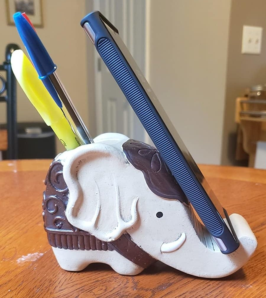 The desk ornament with pens and a phone