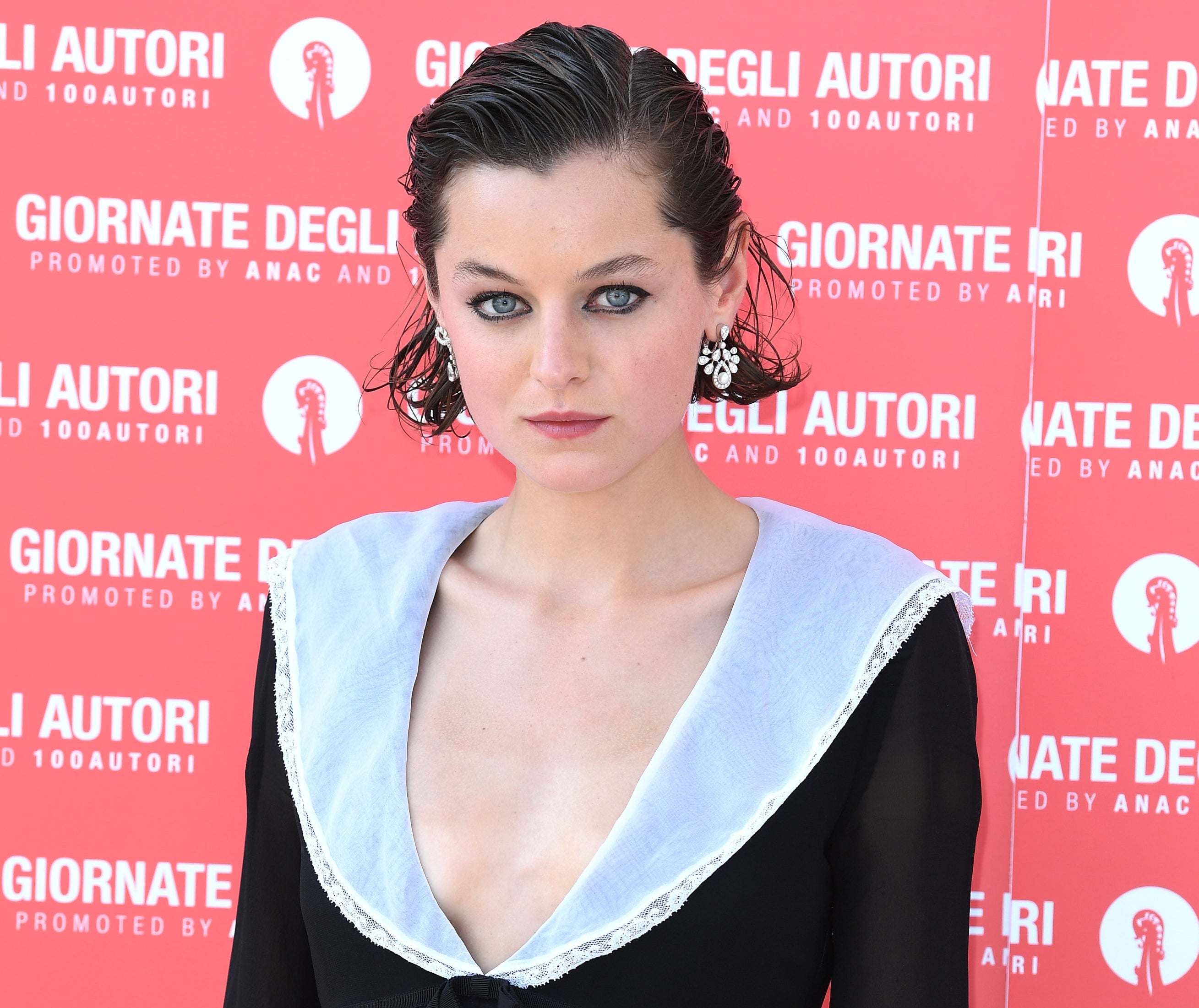 Emma wears a black gown with a plunging black neckline and oversized white collar
