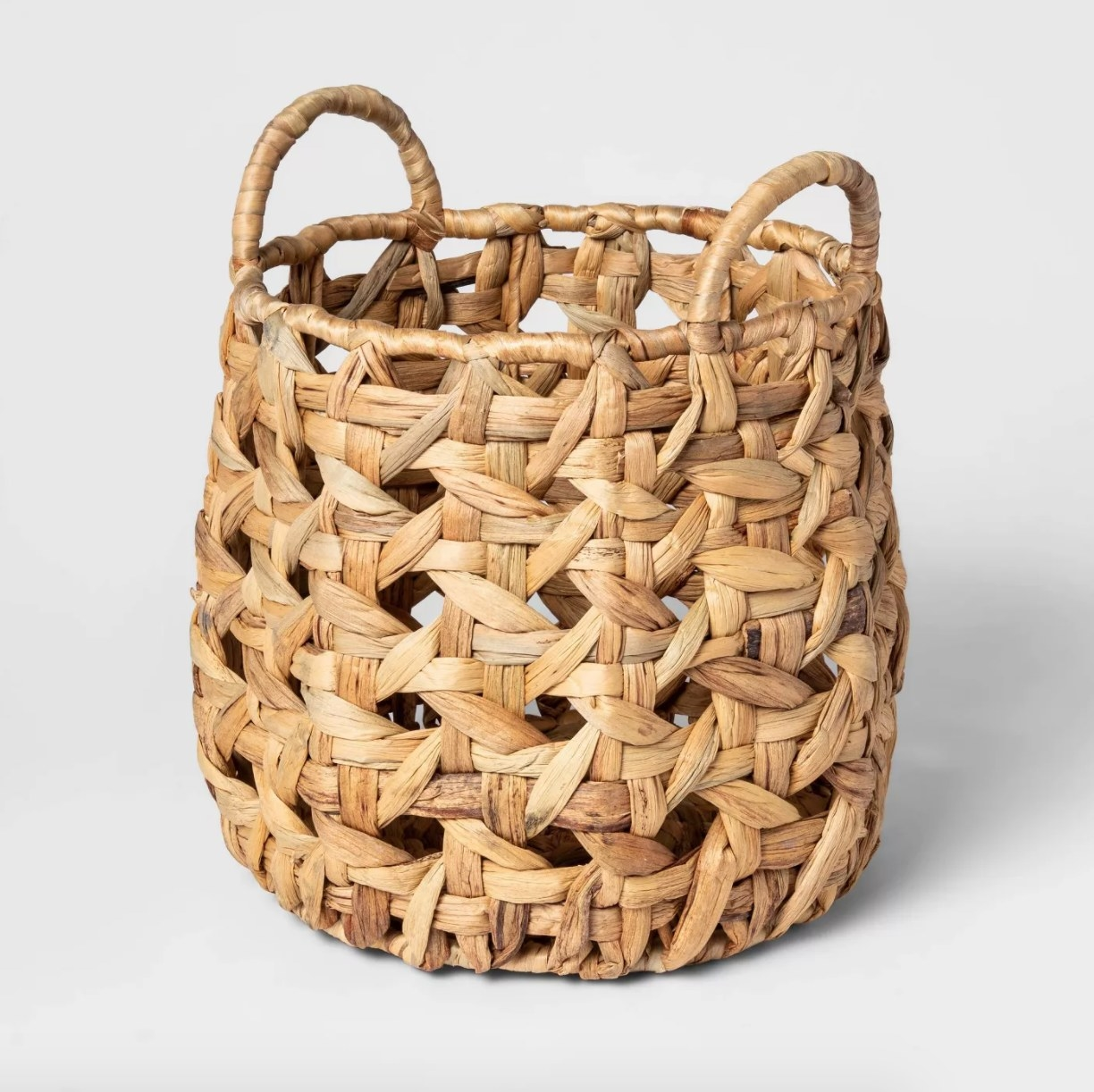 A woven basket made from water hyacinth with handles