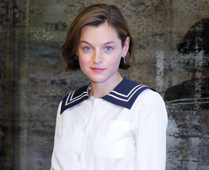 Emma smiles while wearing a white button down with a blue collar