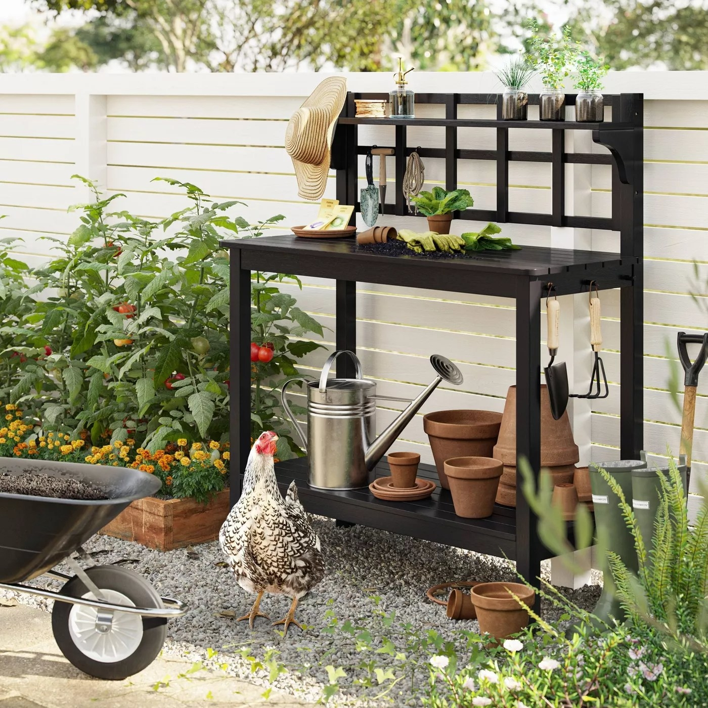 The blackened wood patio bench is outside and surrounded by gardening supplies, a chicken and fresh produce