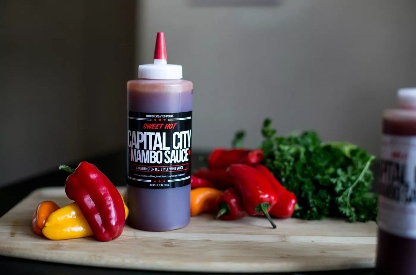 """The bottle of sauce says """"CAPITAL CITY MAMBO SAUCE"""" and is surrounded by peppers and greens"""