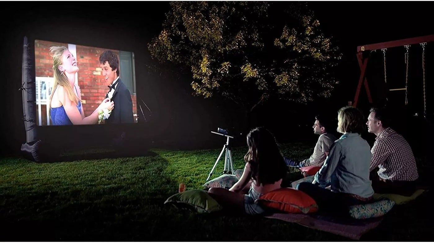 The projector has a lit up movie and there are two children and two adults outdoors at night watching