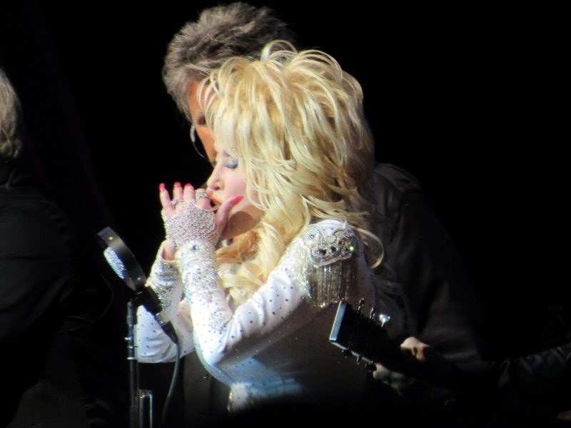 Dolly Parton plays a harmonica during a concert. She wears a bedazzled white outfit and has bright painted pink nails.