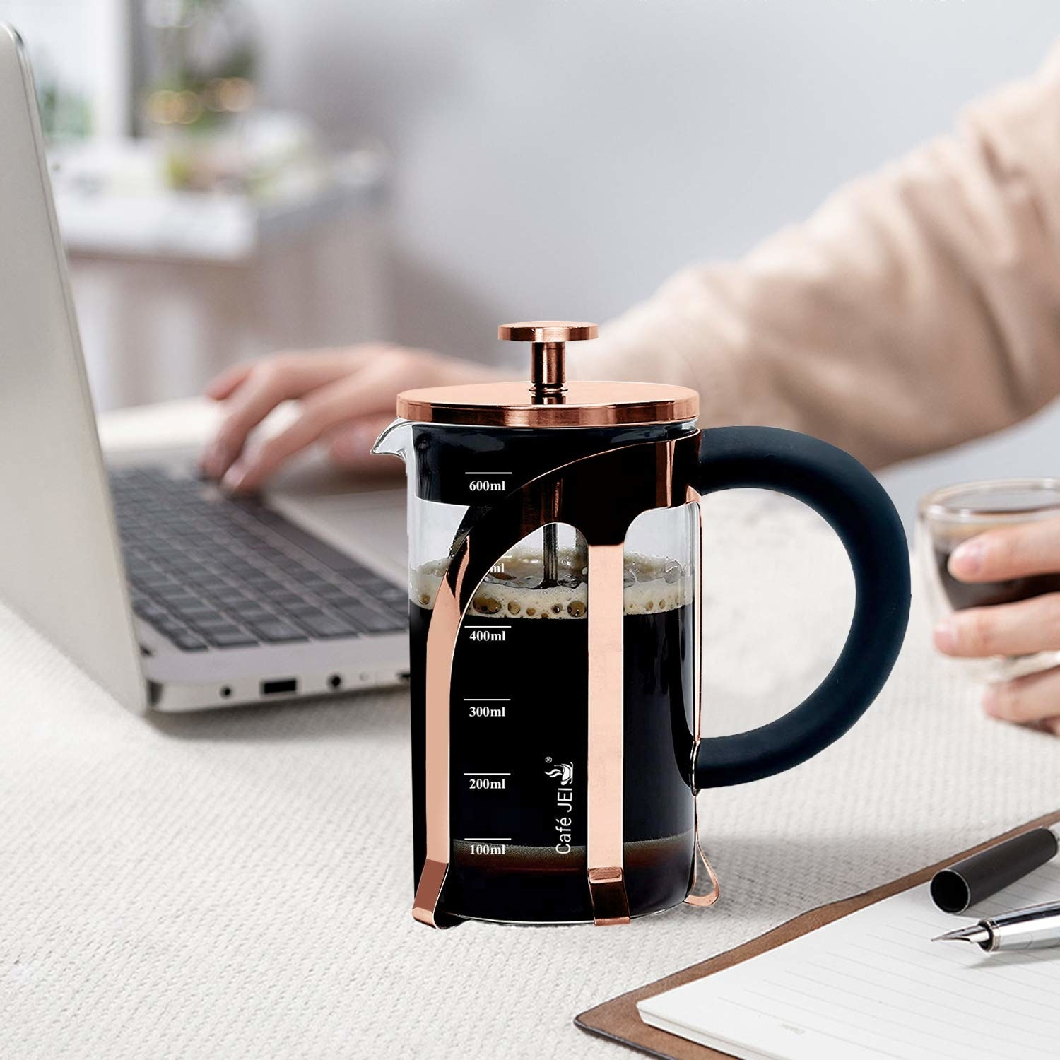 A rose gold french press with coffee, placed on a table with a person working on a laptop in the background.