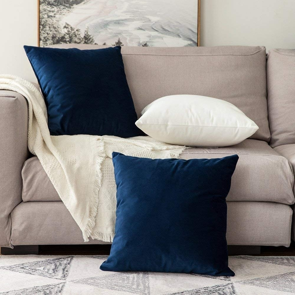 Blue and white velvet cushion covers on a sofa in front of a painting