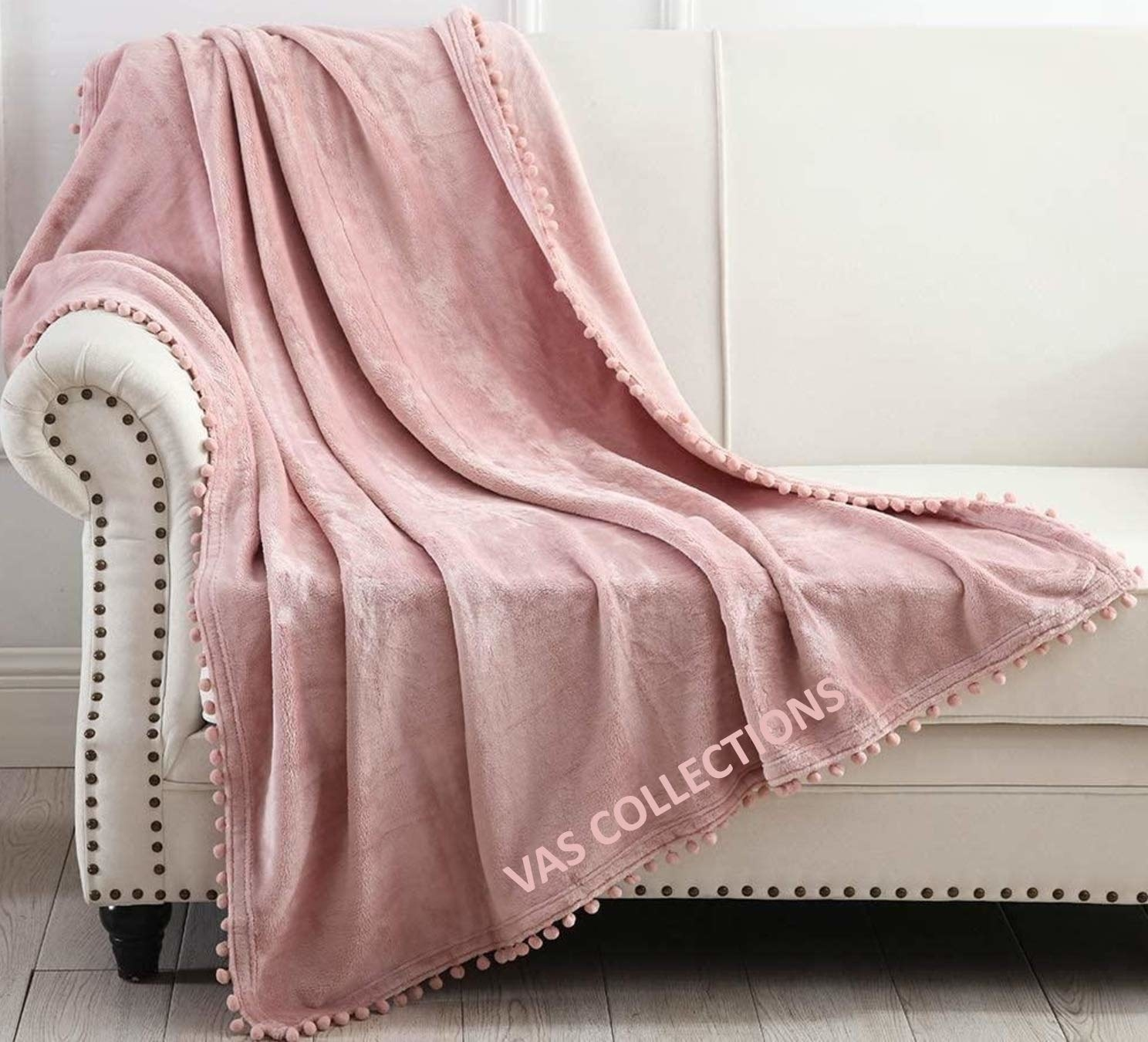A pink throw blanket on a sofa