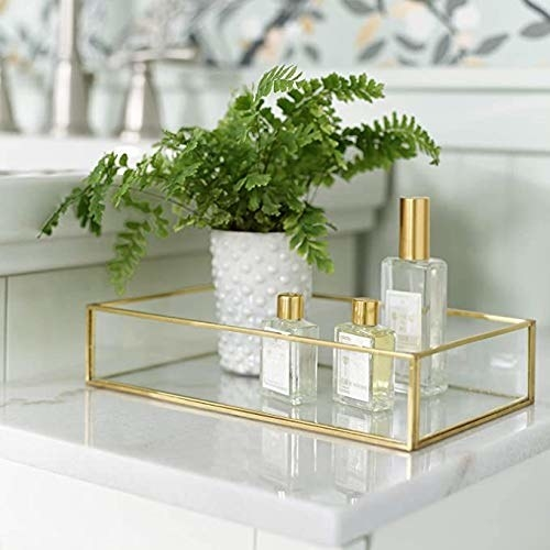 A golden rimmed glass tray with bottles of perfume and a plant in it