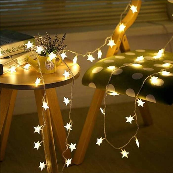 Starry string lights on a table with books on it next to a chair