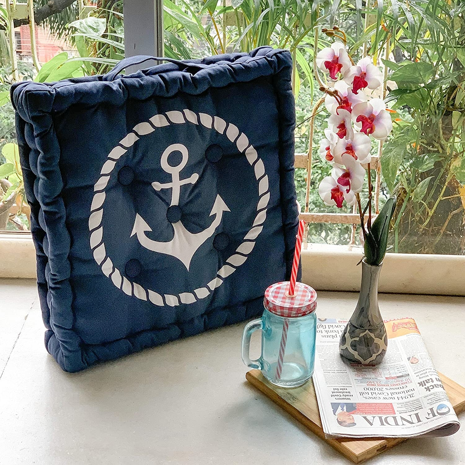A blue anchor pillow next to a mason jar and a stack of newspapers