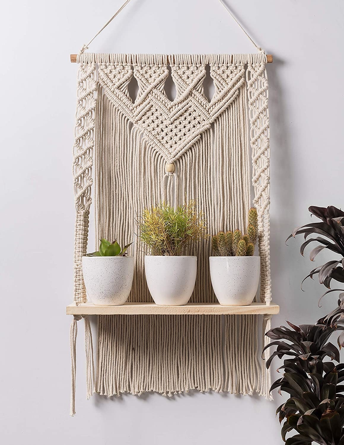 A handwoven Macrame wall hanging shelf with plants on it