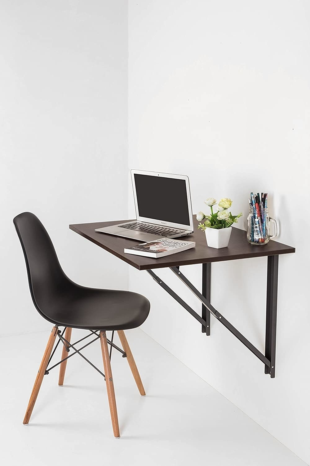 A black folding desk mounted to the wall.