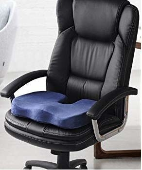 A navy blue memory foam cushion placed on a black office chair.