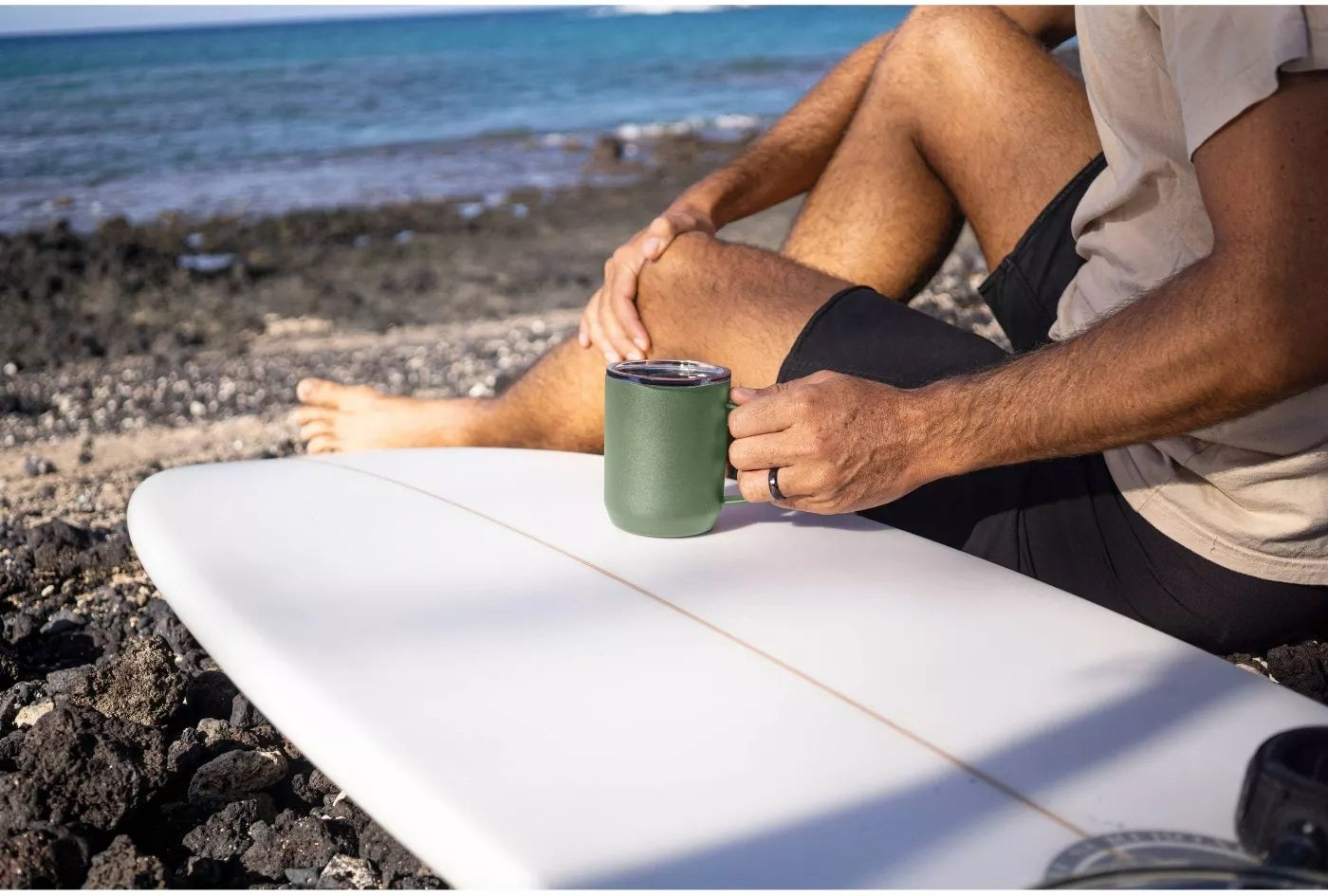 The green mug is in an adult's hand and is resting on a surfboard with a body of water in the background