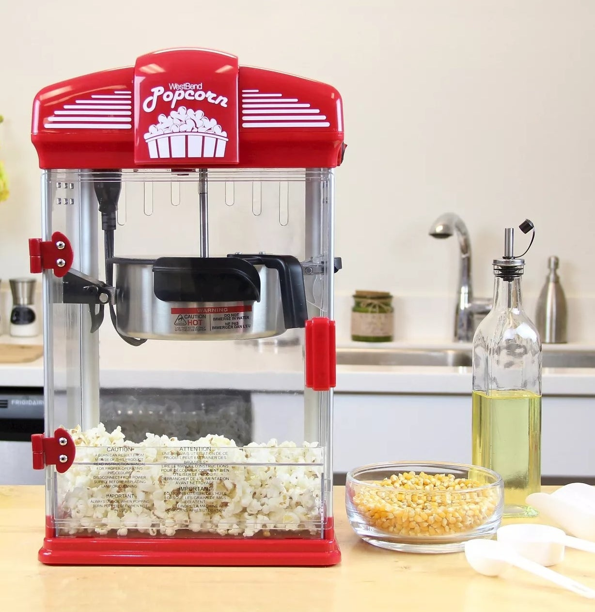 """The machine is red and says """"WestBend"""" """"Popcorn"""" and has kernels and oil surrounding it"""
