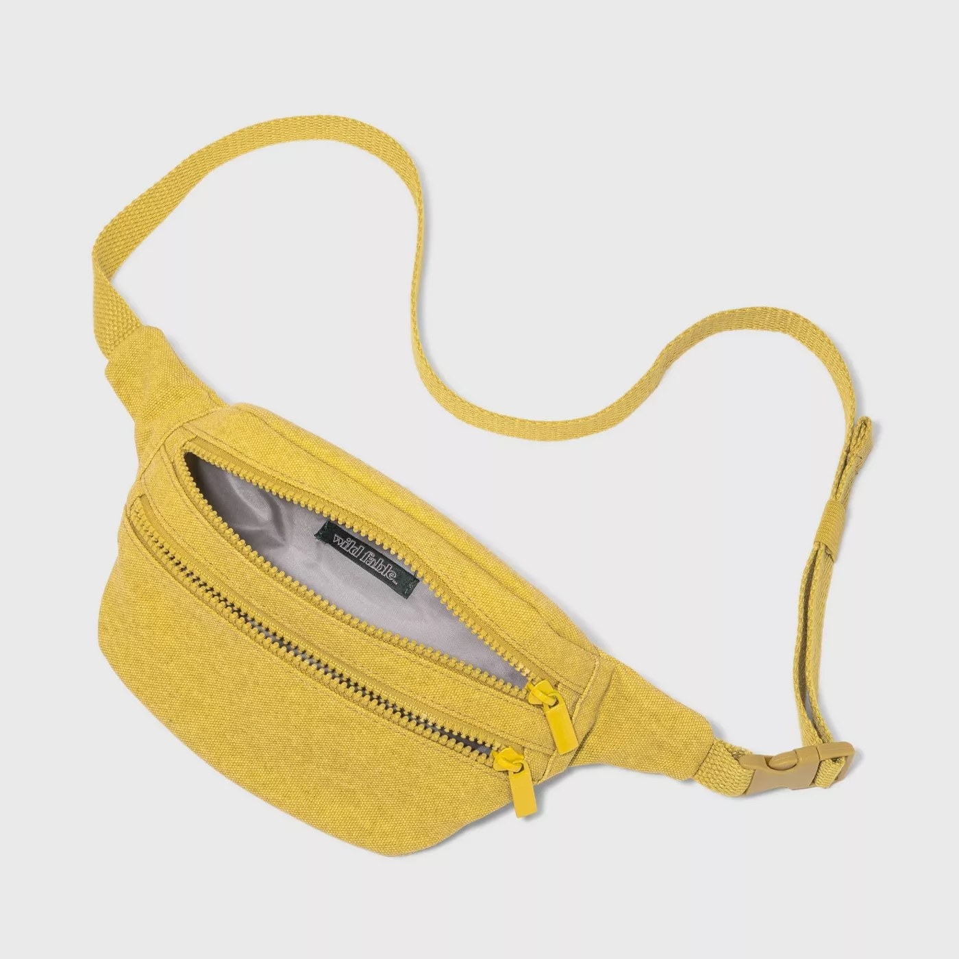"""The yellow fanny pack has two large zips and says """"wild fable"""" on the inside"""