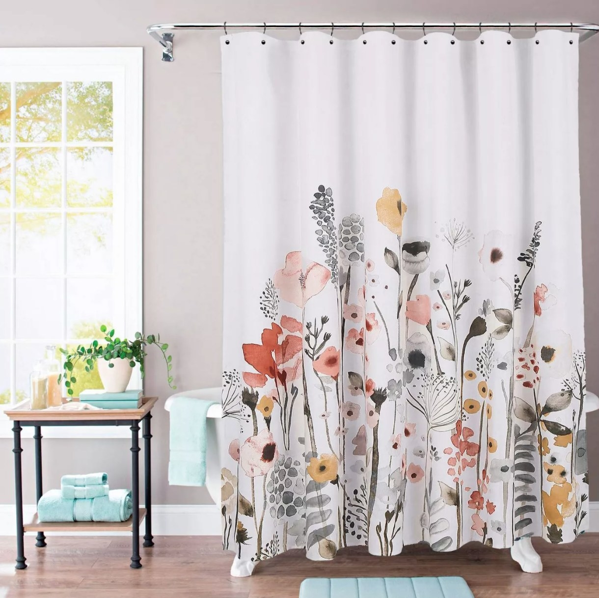 A white shower curtain with gray, pink, and muted yellow design