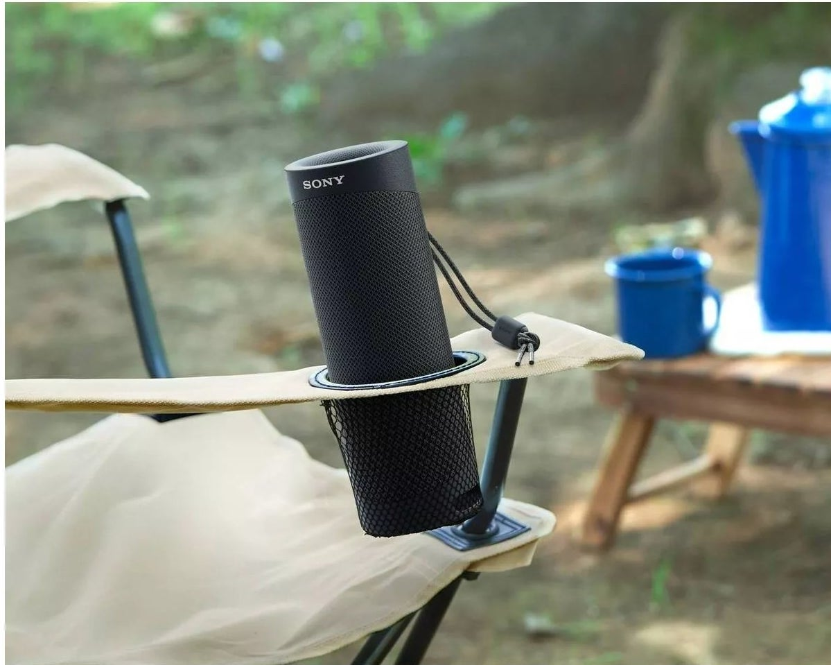 """The black speaker says """"SONY"""" and is in the arm hole of a folding chair at a campsite"""