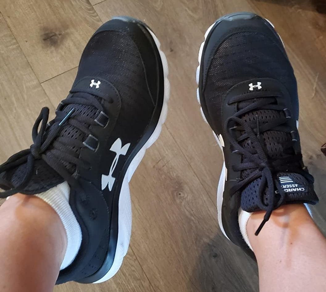 The shoes in black with white detailing, on a reviewer's feet