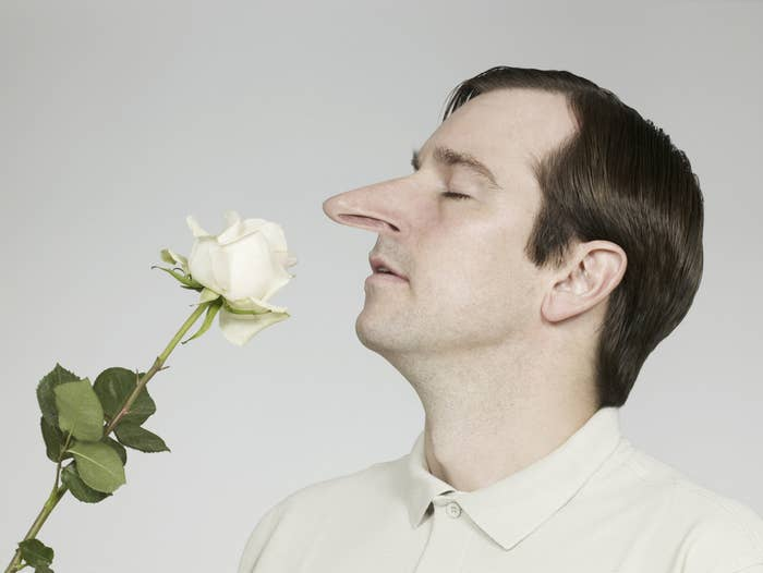 A man with a long nose smells a flower
