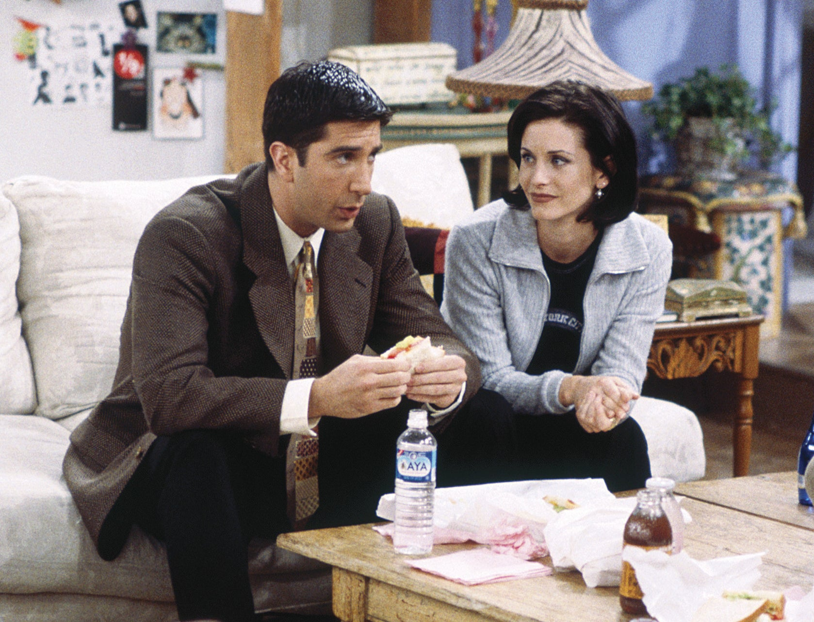 Ross sits on a couch while talking to MOnica