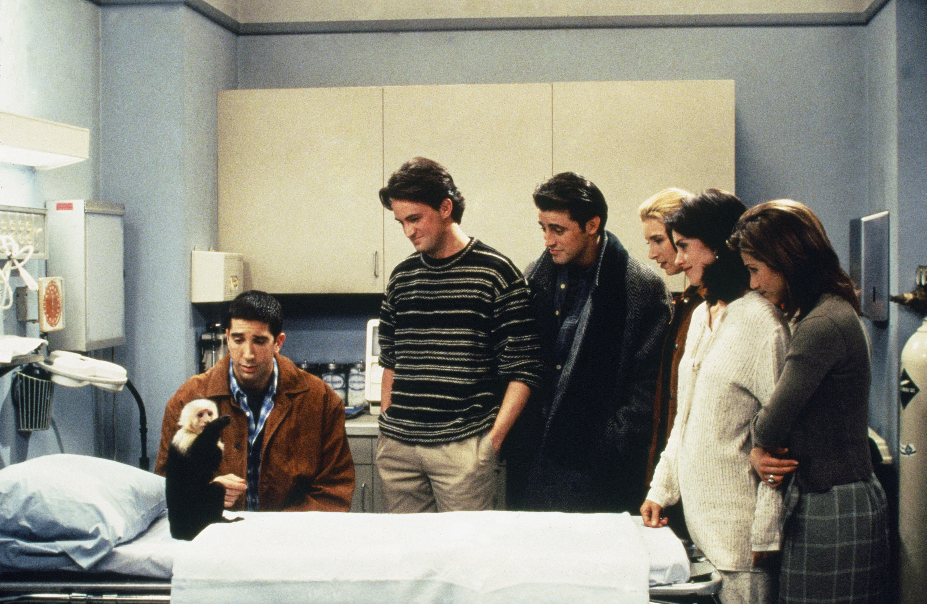 Ross and the rest of the cast look at Marcel while the monkey sits on a doctor's table