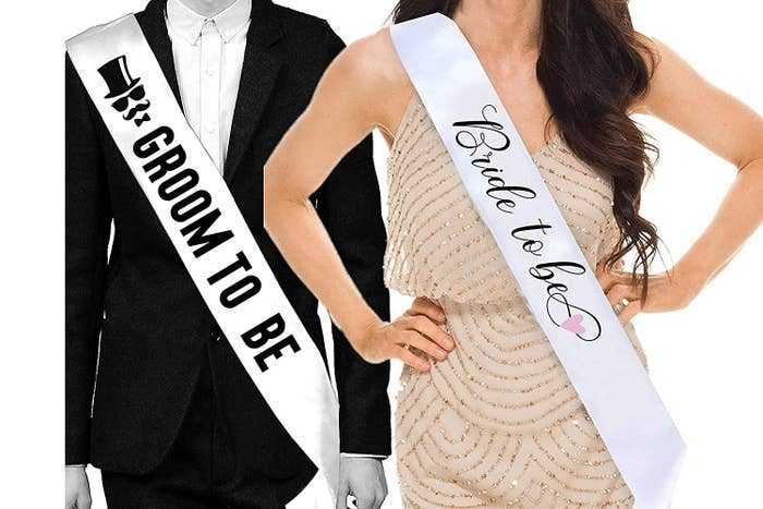 A man and a woman wearing Groom to Be and Bride to Be sashes respectively.