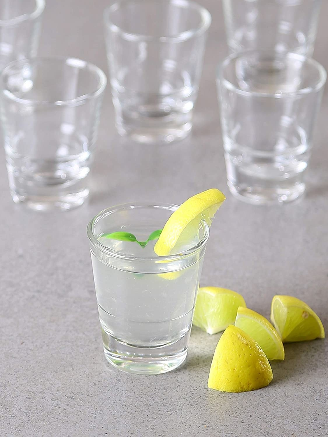 A shot glass with a drink and lemon in it.