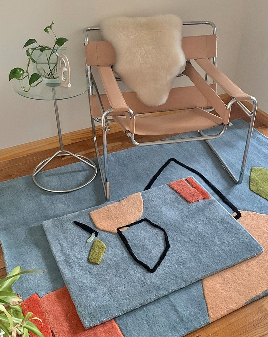"""a small """"limits of communication"""" wool rug on top of a larger one"""