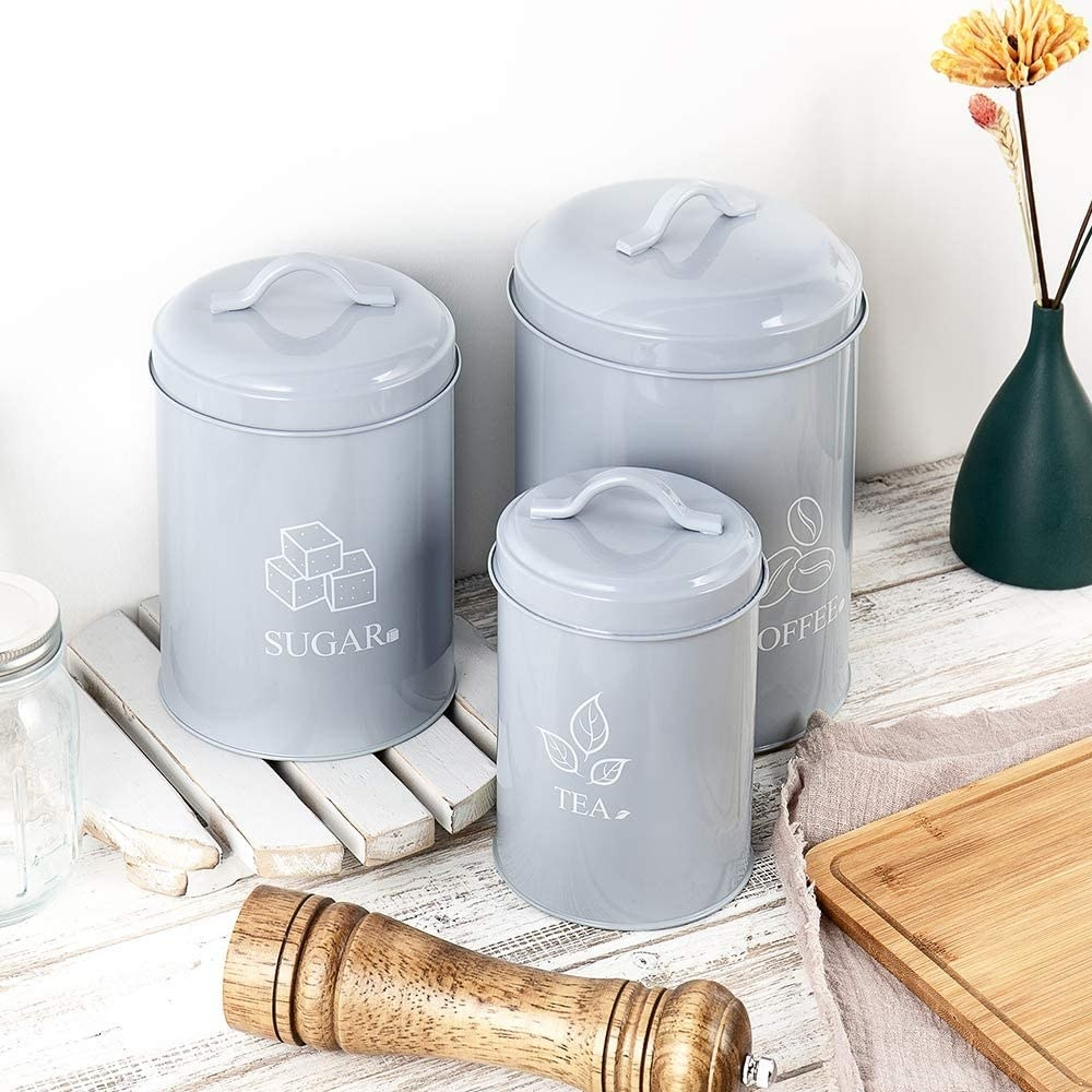 A trio of powder-coated steel canisters on a kitchen counter; they are labelled sugar, coffee, and tea