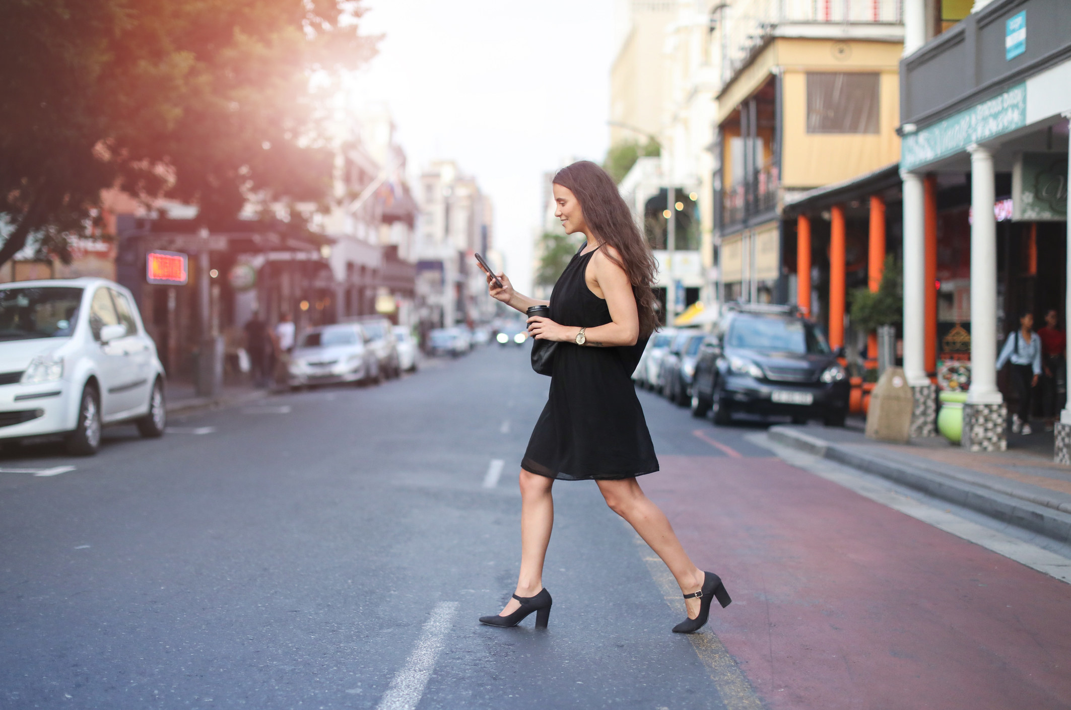 Woman texting and crossing the street