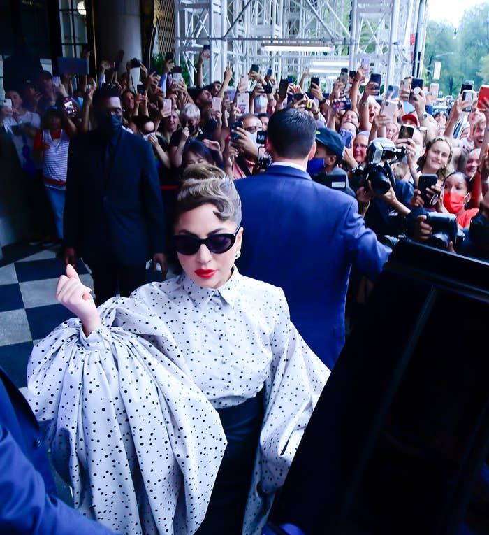 Lady Gaga wears a polka dot blouse with voluminous sleeves and sunglasses as she walks past a crowd of fans